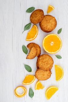 Uma vista de cima de biscoitos com sabor de laranja com fatias de laranja frescas no biscoito de mesa leve