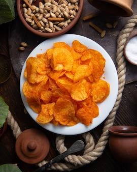 Uma vista de cima de chips de laranja quente dentro de um prato branco com amendoim na mesa de madeira salgadinhos sal de especiarias