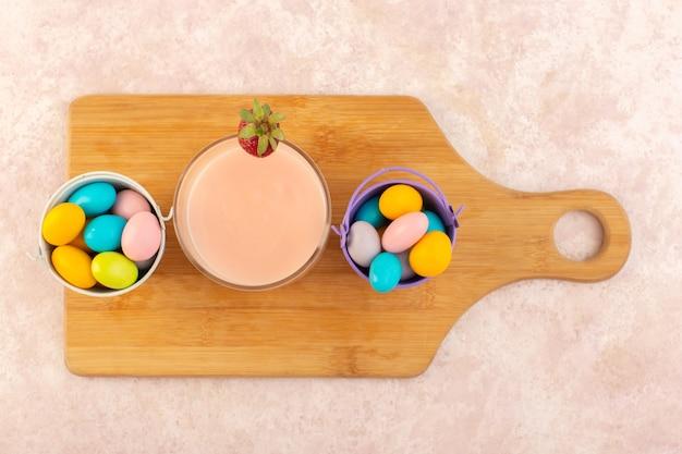 Uma vista de cima de doces coloridos com sobremesa de morango