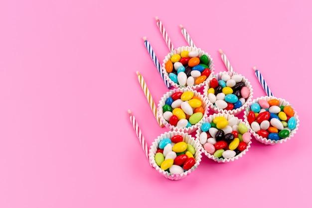 Uma vista de cima de doces coloridos dentro de pacotes de papel junto com velas em rosa