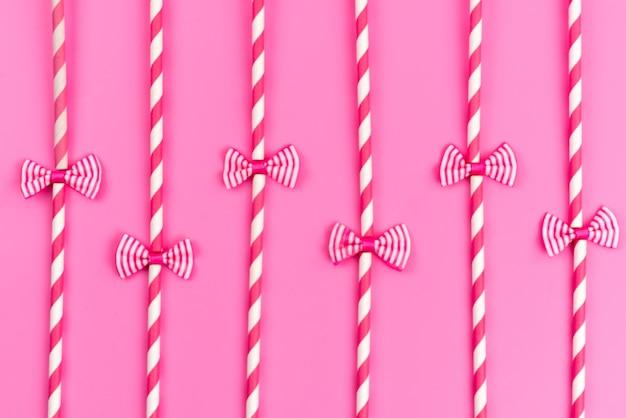 Uma vista de cima de doces em forma de palito rosa-branco com laços na cor rosa doce