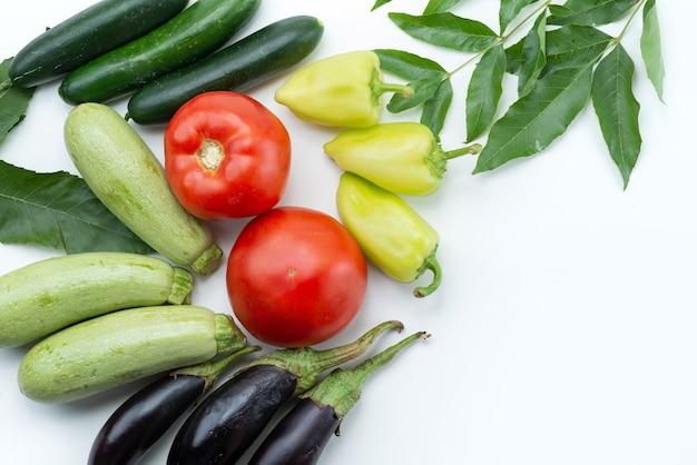 Uma vista de cima de vegetais frescos, como tomates vermelhos, abóbora e berinjela em alimentos de cor branca e vegetal