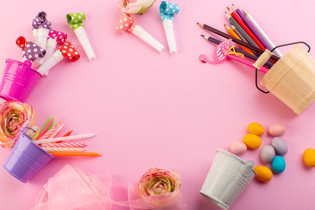 Uma vista de cima de velas e lápis junto com flores e doces na mesa rosa com uma foto de decoração de aniversário
