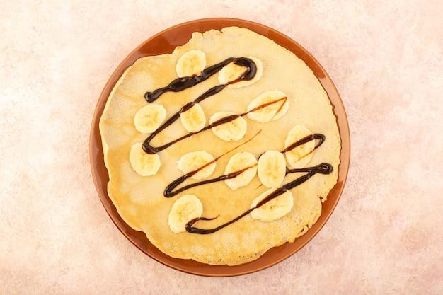 Uma vista de cima deliciosas panquecas elaboradas com chocolate e bananas dentro de um prato redondo na mesa rosa