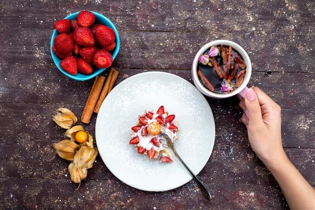 Uma vista de cima delicioso pequeno bolo com creme e frutas frescas fatiadas junto com canela e morangos na mesa marrom bolo de frutas chá de biscoito