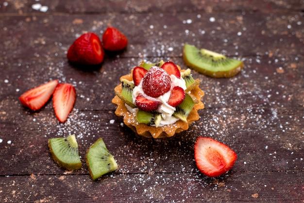 Uma vista de cima delicioso pequeno bolo com creme e frutas frescas fatiadas no biscoito de bolo de frutas marrom