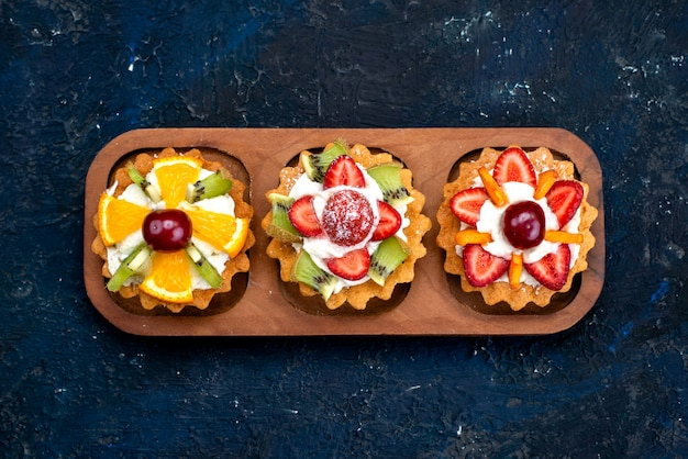 Uma vista de cima diferentes bolinhos com creme e frutas frescas fatiadas no chá de biscoito de bolo de frutas azul fundo Foto gratuita