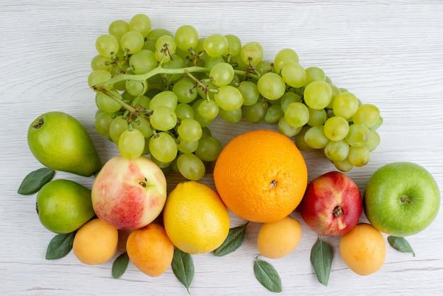 Uma vista de cima diferentes frutas frescas e suaves, como damasco, uvas, maçãs na mesa branca, composição de frutas vitamina de cor