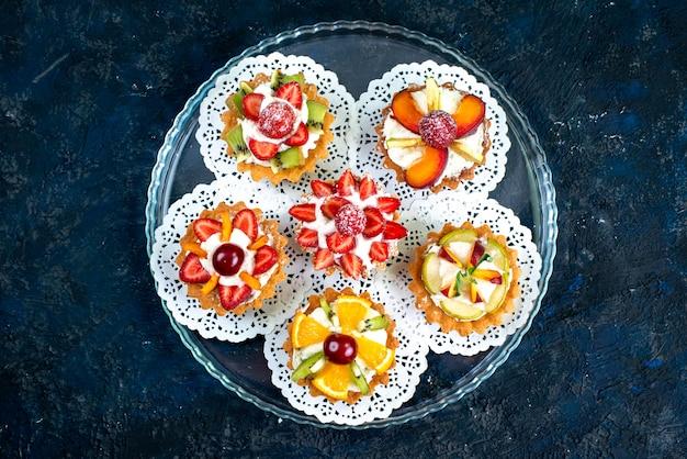 Uma vista de cima diferentes pequenos bolos com creme e frutas frescas fatiadas no bolo de frutas cinza-azulado