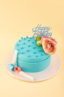 Uma vista de cima do bolo de aniversário azul com uma flor no topo da mesa amarela.