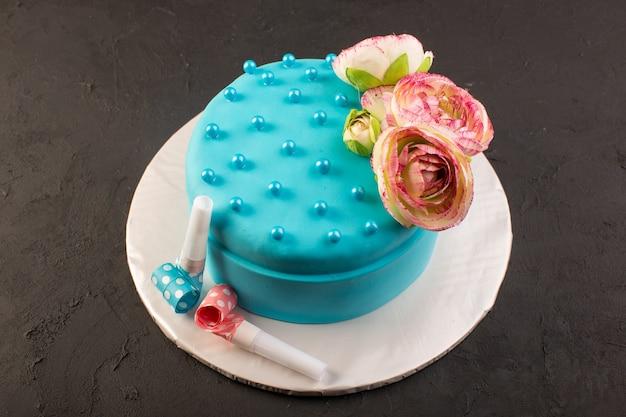 Uma vista de cima do bolo de aniversário azul com uma flor no topo da mesa escura.