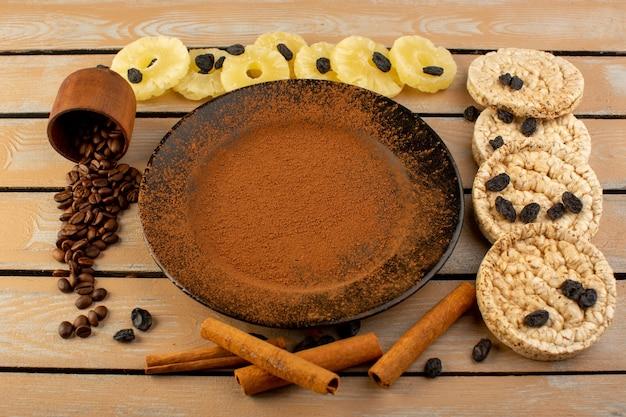 Uma vista de cima do café em pó marrom dentro de uma placa preta com abacaxi seco, canela e biscoitos na mesa rústica de creme de café com sementes de café.