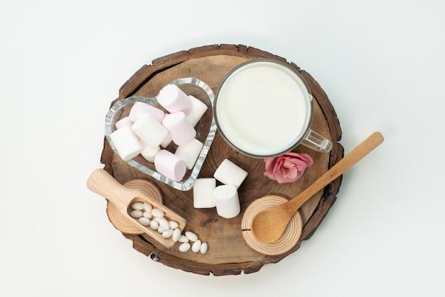 Uma vista de cima do marshmallow e do leite em uma madeira marrom e branca, doces de açúcar