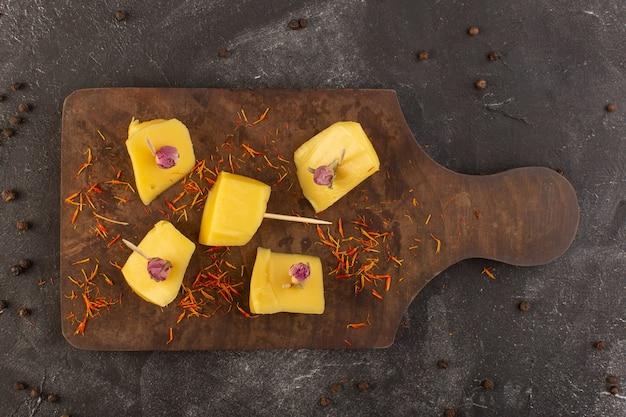 Uma vista de cima do queijo amarelo fresco com sementes de café marrom na mesa cinza.