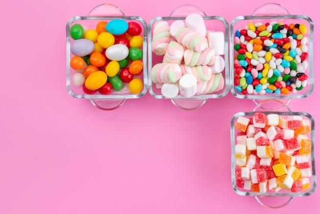 Uma vista de cima doces coloridos com geleias dentro de copos em uma mesa rosa, arco-íris colorido