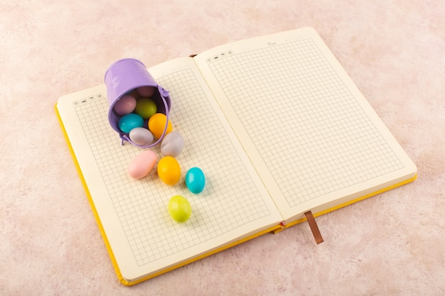Uma vista de cima. doces coloridos espalhados por todo o caderno e doces rosa de mesa.
