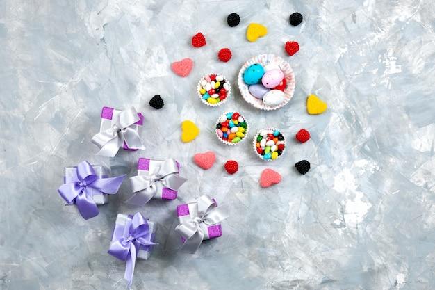 Uma vista de cima doces coloridos junto com marmeladas em forma de coração. pequenas caixas roxas de presente com arcos no fundo cinza.