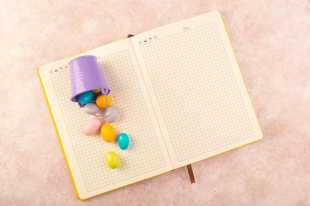 Uma vista de cima dos doces coloridos com um caderno na mesa rosa.