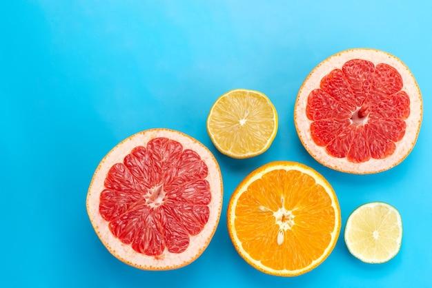 Uma vista de cima em fatias cítricas, toranjas, laranjas e limões na mesa azul, suco de frutas cítricas
