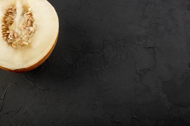 Uma vista de cima em fatias de melão fresco e polpudo doce isolado no escuro