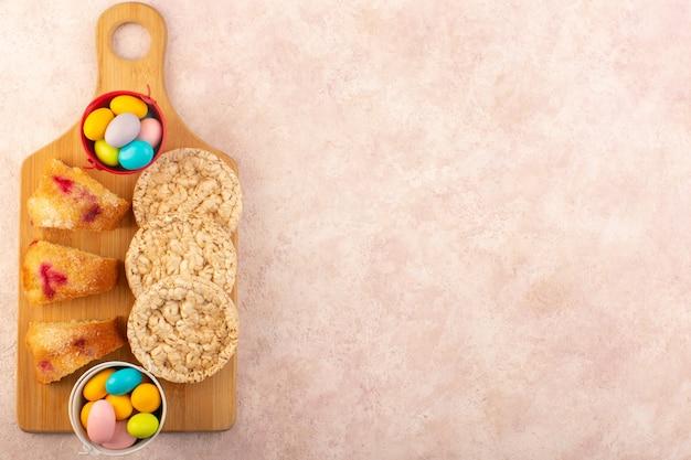 Uma vista de cima fatias de bolo de cereja com doces e biscoitos na mesa rosa bolo de açúcar