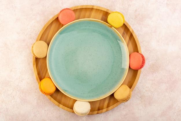Uma vista de cima forrada de macarons franceses na mesa rosa bolo biscoito açúcar doce