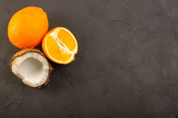 Uma vista de cima laranja suculenta inteira e frutas maduras fatiadas junto com coco fatiado no fundo escuro suco de frutas cítricas