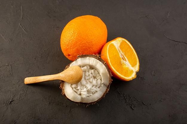 Uma vista de cima, laranjas frescas, frutas sumarentas e suculentas, juntamente com coco fatiado no fundo escuro.