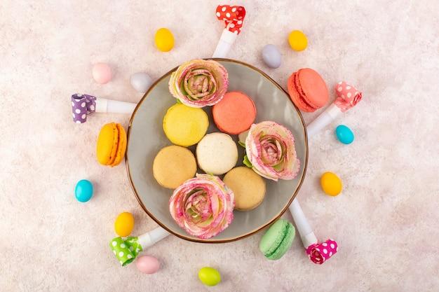 Uma vista de cima, macarons franceses coloridos com doces e flores na mesa rosa, bolo doce açúcar