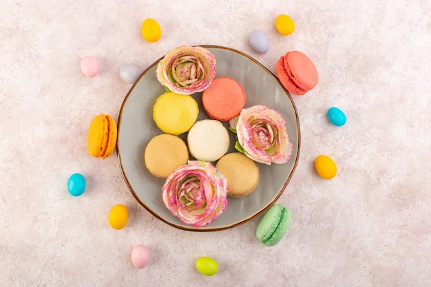 Uma vista de cima macarons franceses coloridos com rosas na mesa rosa bolo biscoito açúcar doce