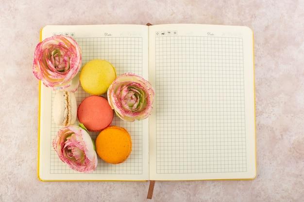 Uma vista de cima, macarons franceses coloridos com rosas no caderno e bolo de mesa rosa com açúcar doce