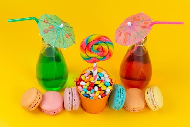 Uma vista de cima, macarons franceses coloridos junto com doces e bebidas diferentes em amarelo, biscoito de bolo doce