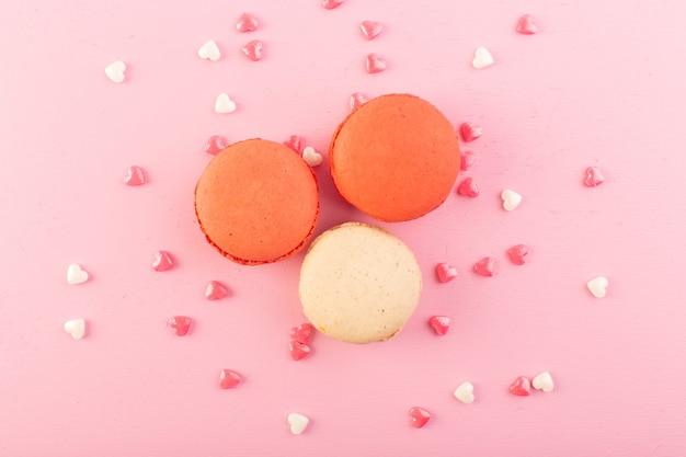 Uma vista de cima macarons franceses coloridos no bolo de mesa rosa biscoito açúcar doce