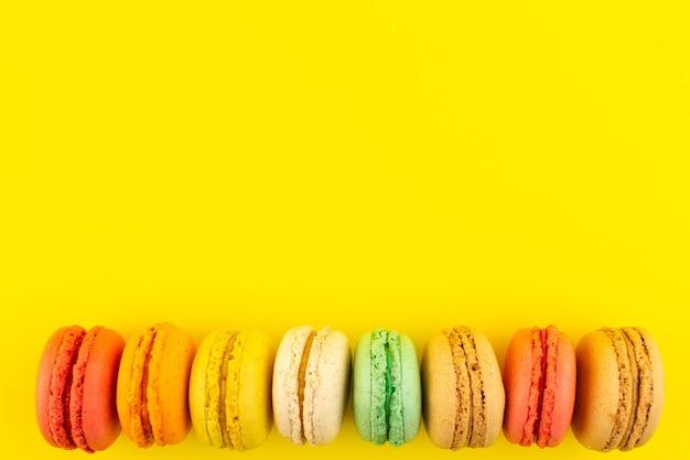 Uma vista de cima, macarons franceses coloridos saborosos na mesa amarela, bolo de açúcar biscoito doce