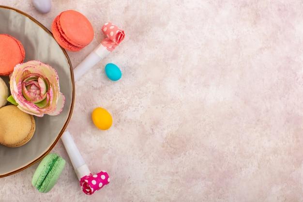 Uma vista de cima, macarons franceses coloridos saborosos na mesa rosa, bolo de açúcar, biscoito doce