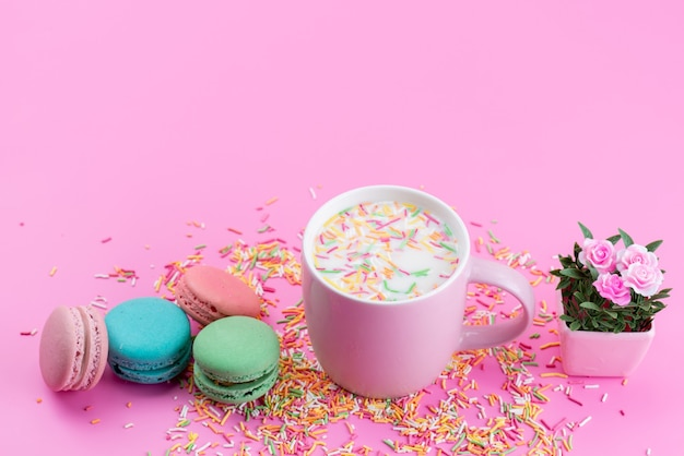 Uma vista de cima, macarons franceses junto com partículas de doces coloridas, tudo em rosa, bolo de chão com açúcar