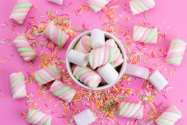 Uma vista de cima marshmallows rosa-brancos doces e pegajosos junto com partículas de doces coloridas em rosa