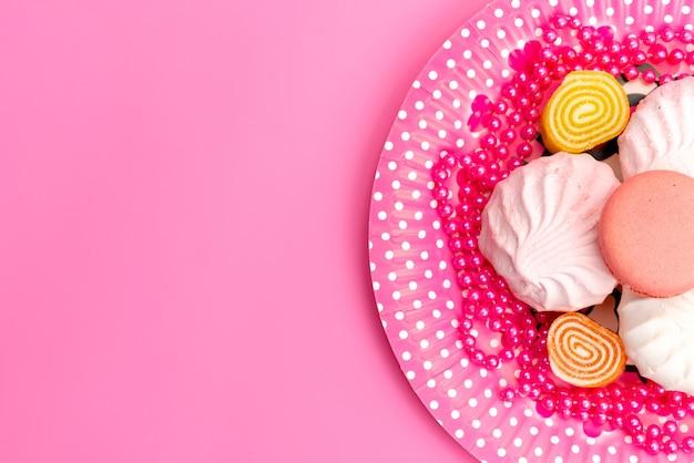 Uma vista de cima, merengues e geléias dentro de rosa, prato em rosa, bolo de biscoito de açúcar