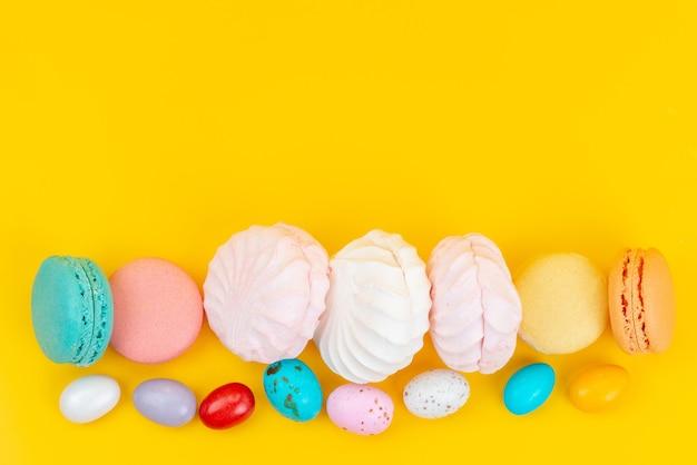 Uma vista de cima, merengues e macarons deliciosos e doces em amarelo, cor de doce de arco-íris