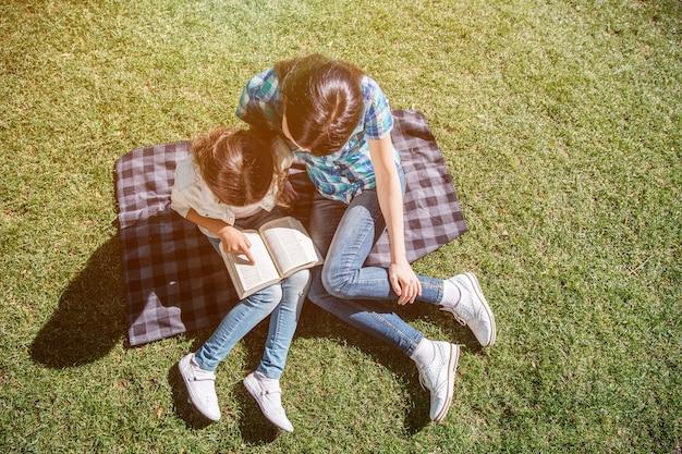 Uma vista de cima, onde mãe e filho estão sentados juntos no cobertor e olhando para o livro. eles estão lendo isso. pequena menina está segurando este livro aberto.