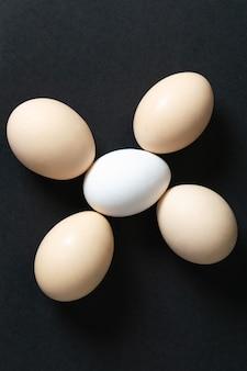 Uma vista de cima ovos brancos crus inteiros no escuro