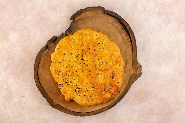 Uma vista de cima pão assado saboroso quente na mesa de madeira marrom