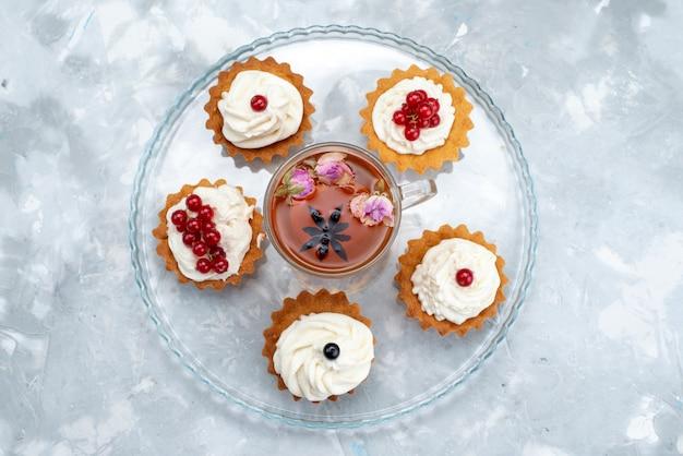 Uma vista de cima, pequenos bolos com creme com cranberries vermelhos e chá no bolo de mesa cinza-azulado