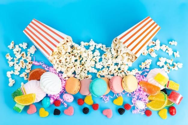 Uma vista de cima, pipoca e macarons, marmeladas coloridas, doces e outros doces
