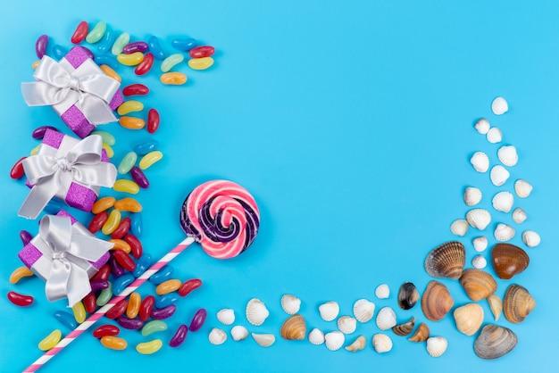 Uma vista de cima, pirulitos e geleias coloridas doces junto com conchas do mar no azul, confeitaria doce de açúcar