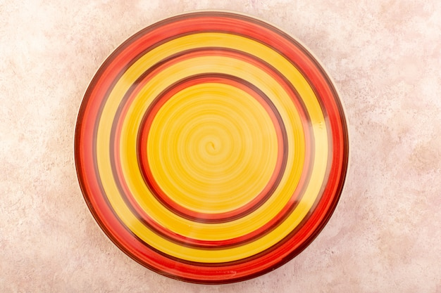 Uma vista de cima prato redondo colorido copo vazio feito mesa de refeição isolada cor