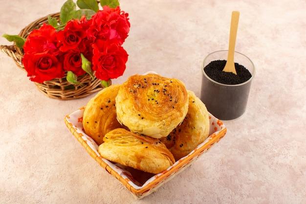 Uma vista de cima qogals assados pãezinhos assados orientais frescos e quentes dentro da caixa de pão junto com flores vermelhas e pimenta na mesa e rosa