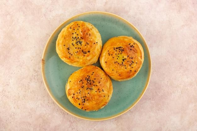 Uma vista de cima qogals assados redondos em forma saborosa e recém-saídos do forno dentro de um prato verde