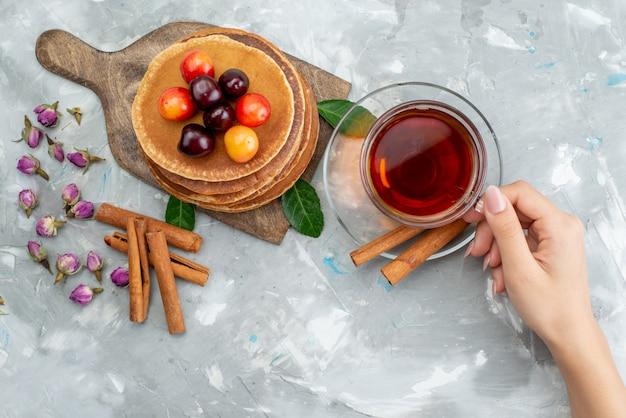 Uma vista de cima redonda panquecas assadas e deliciosas com cerejas e fêmeas segurando chá na mesa de luz