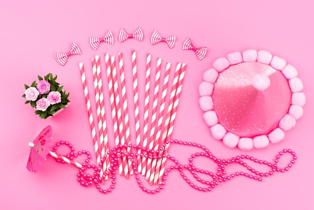 Uma vista de cima rosa-branco em forma de bastão de doces junto com uma tampa de aniversário em rosa bonito, laços em rosa, cor de aniversário